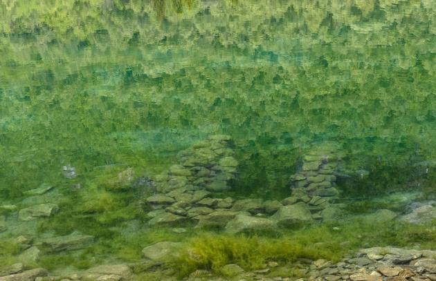Her ser du ruiner under vannskorpen. Et jord og steinras fra fjellet Keipen i 1908 fyllte opp dalbunnen og sperret elva Lygna og satte flere gårder under vann. Det var heldigvis ikke folk eller fe i området akkurat da.